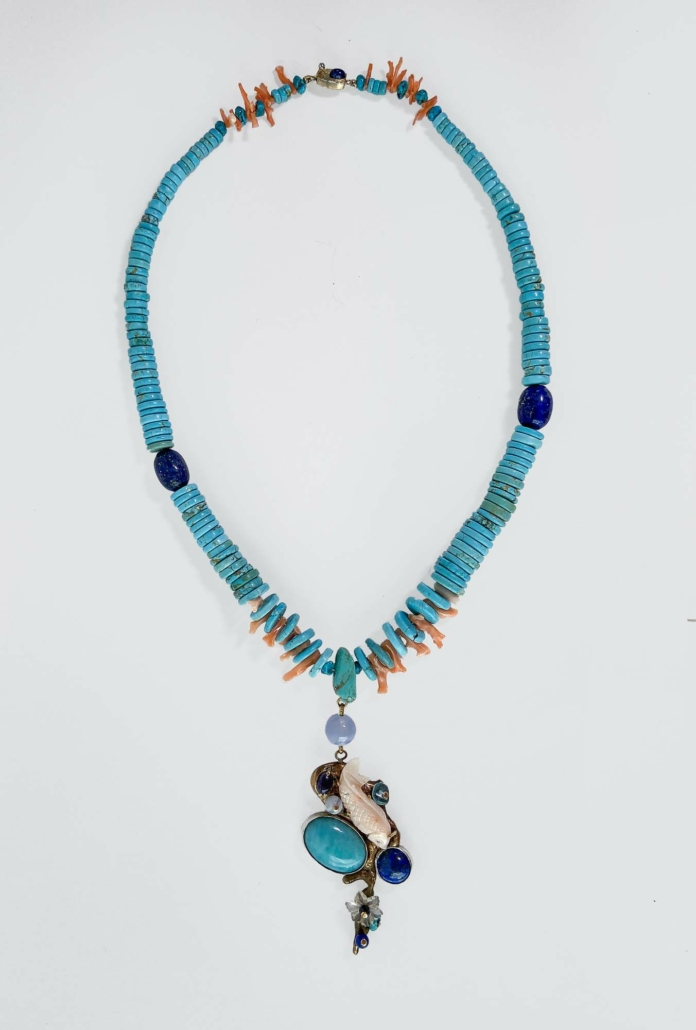 Flowing Water Necklace, 2021, Bronze, Brass, Silver, Turquoise, found antique coral fish, pink branch coral, Lapiz Lazuli, Lolite, Amazonite, Apatite, carved crystal, lace agate. Total length with Chain - 22.5in Center medalion - 3.25 l x 1.5 w inches